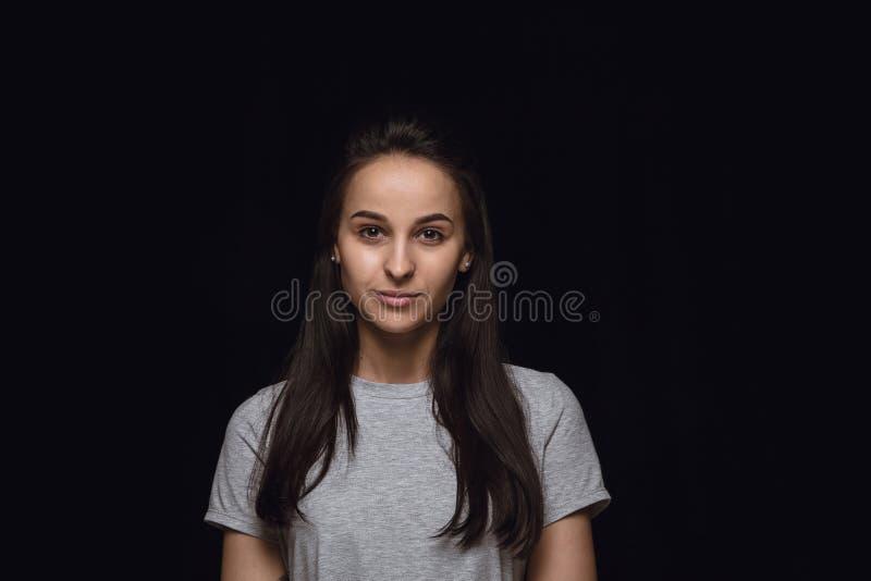 Ritratto alto vicino della giovane donna isolato sul fondo nero dello studio immagini stock libere da diritti