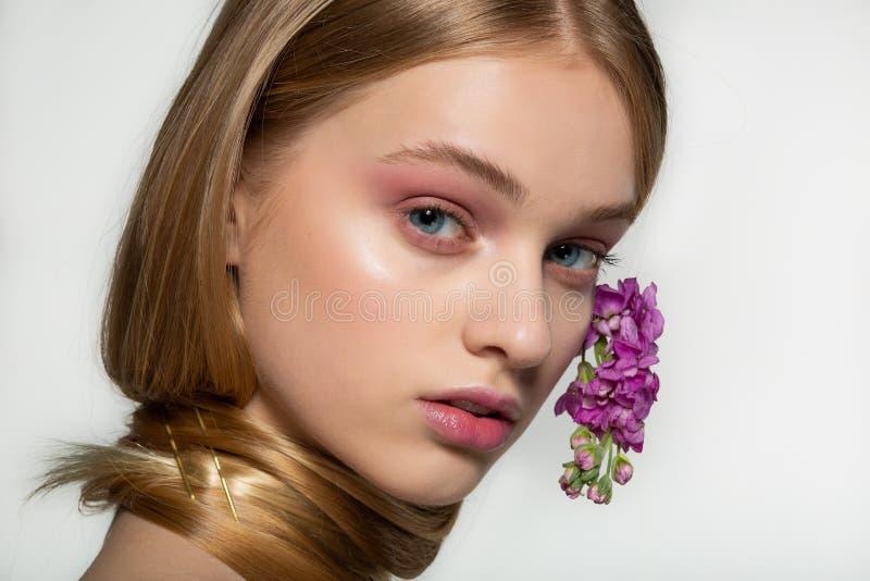 Ritratto alto vicino della ragazza con gli occhi azzurri, trucco luminoso, collo avvolto in capelli, fiori porpora arricciati in  immagini stock libere da diritti