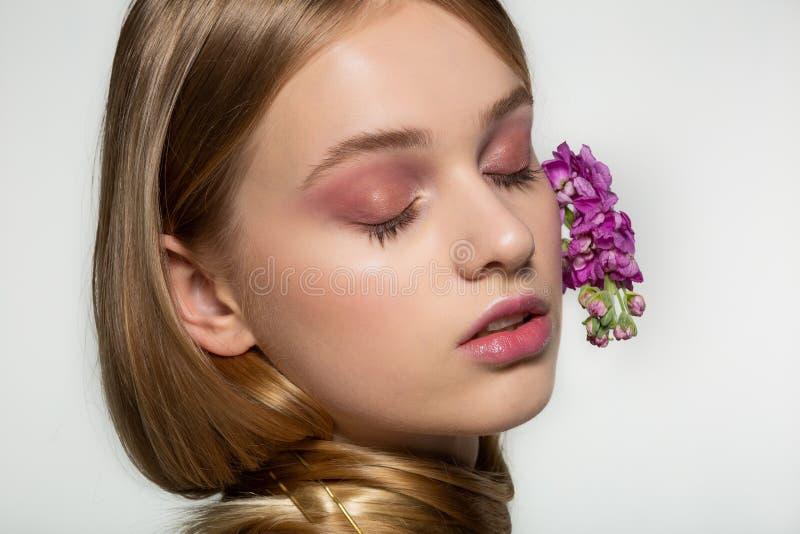 Ritratto alto vicino della ragazza con gli occhi chiusi, trucco luminoso, collo avvolto in capelli, fiori porpora arricciati in c fotografie stock libere da diritti