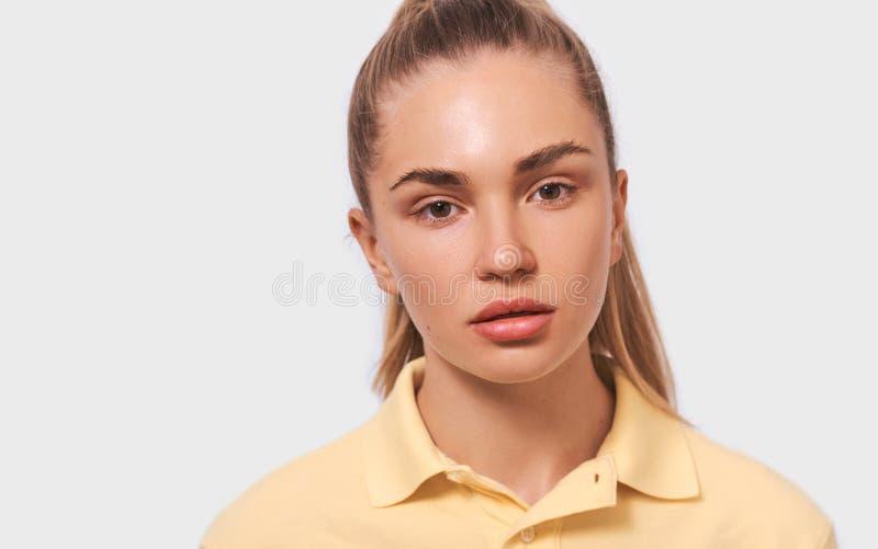 Ritratto alto vicino dello studio di bella giovane donna bionda con pelle pulita sana in maglietta gialla che esamina la macchina fotografie stock