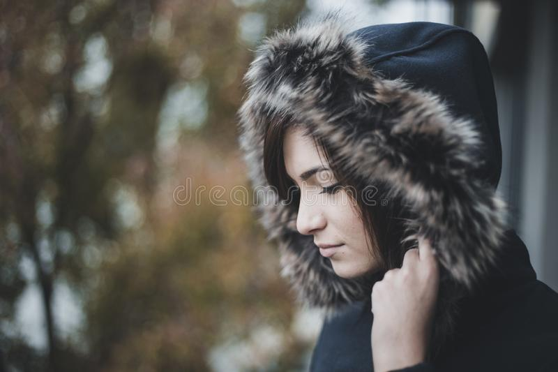 Ritratto alto vicino di autunno di giovane e donna sveglia in giacca blu con il cappuccio simile a pelliccia sulla sua testa Raga fotografia stock libera da diritti