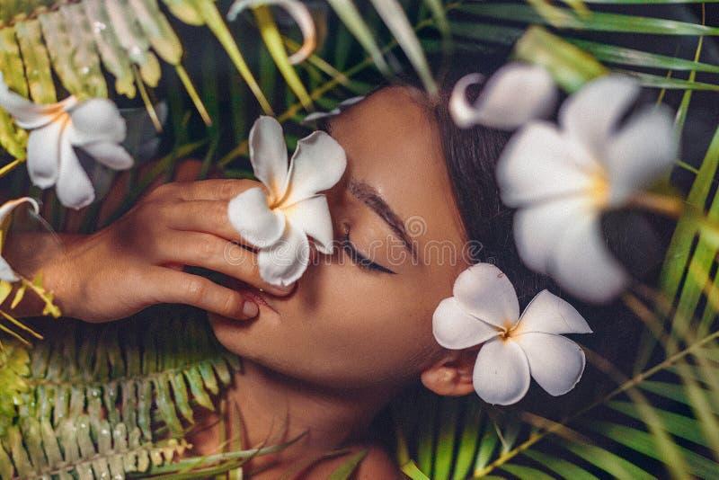 Ritratto alto vicino di bella donna con i fiori del frangipane fotografia stock libera da diritti