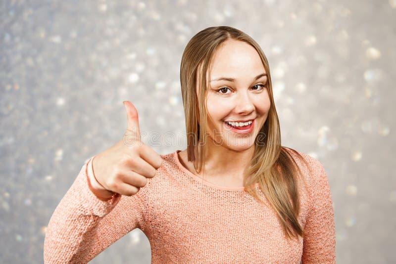 Ritratto alto vicino di bella giovane donna sorridente in una camicia beige che guarda e che mostra pollice su, su un fondo delle fotografia stock libera da diritti
