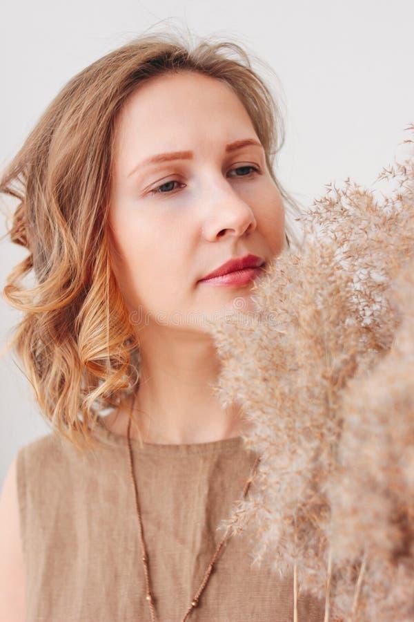 Ritratto alto vicino di bella giovane donna in vestito di tela con i fiori secchi, concetto naturale di bellezza di eco fotografie stock