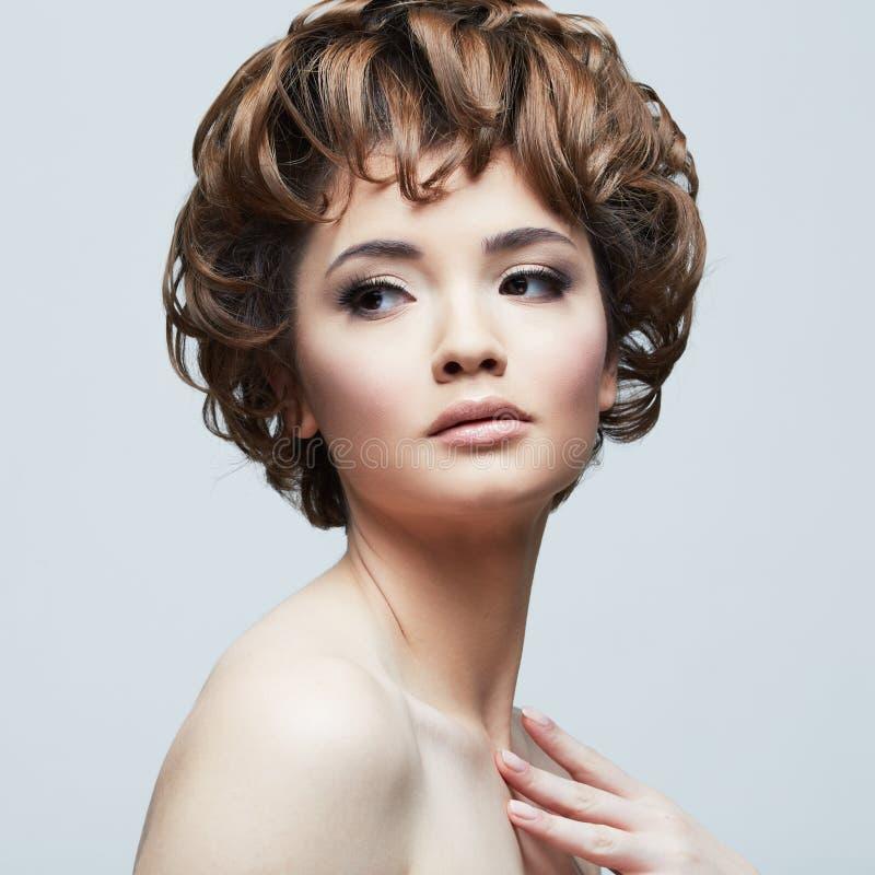 Ritratto alto vicino di bellezza del fronte della giovane donna su fondo bianco fotografia stock