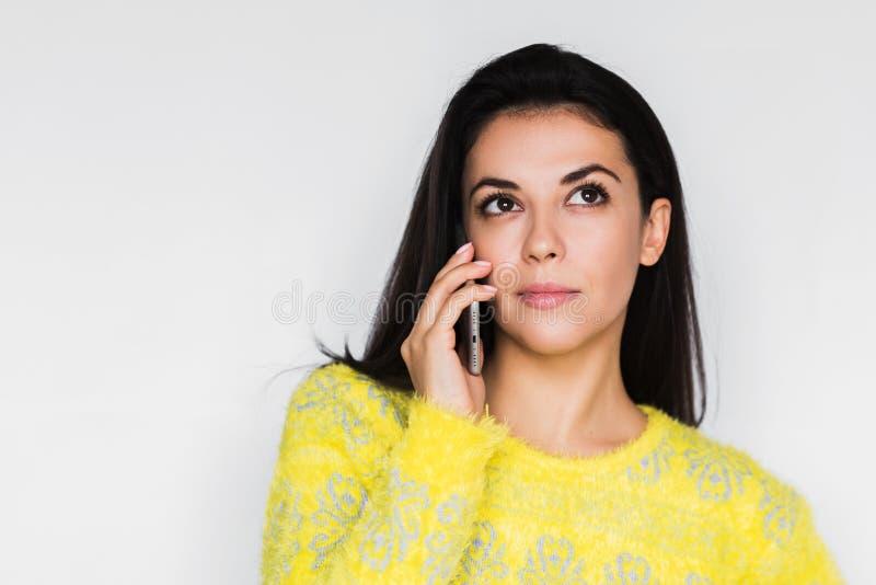 Ritratto alto vicino di giovane bella donna seria che per mezzo dello Smart Phone sopra fondo grigio chiaro immagine stock libera da diritti