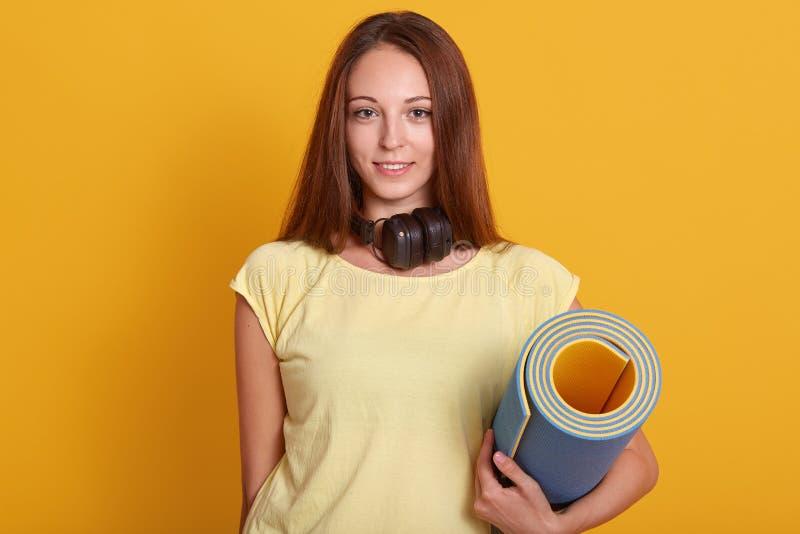 Ritratto alto vicino di giovane donna attraente con l'ente perfetto, delle cuffie d'uso intorno al collo e della maglietta gialla fotografie stock libere da diritti
