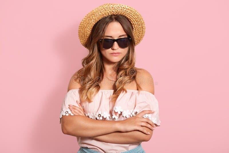 Ritratto alto vicino di giovane donna dai capelli giusta che indossa camicia, il cappello di paglia e gli occhiali da sole rosa,  fotografie stock libere da diritti