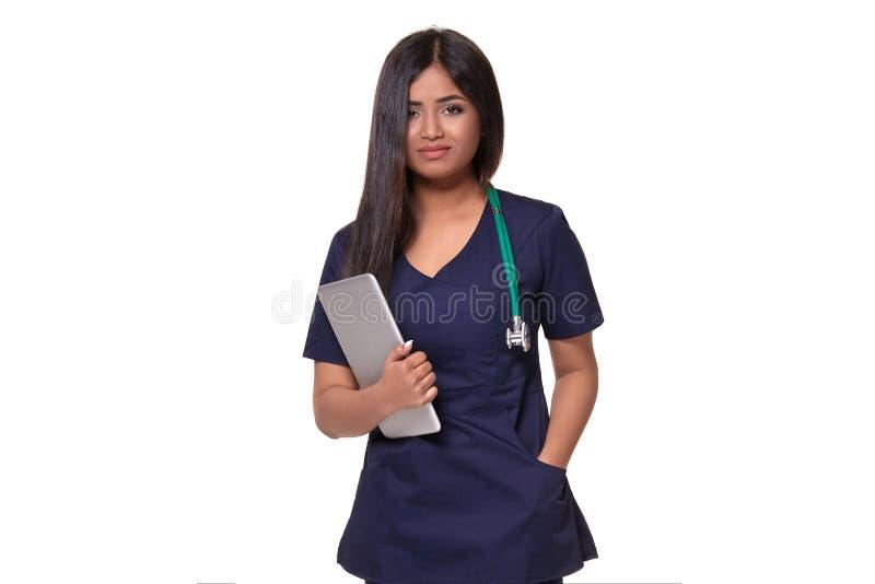 Ritratto alto vicino di giovane donna indiana di medico con lo stetoscopio intorno al collo isolato su fondo bianco fotografia stock