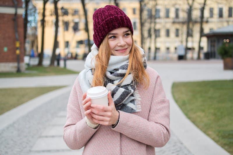Ritratto alto vicino di giovane ragazza bionda alla moda in cappello rosso che tiene la tazza di caffè da portar via fotografia stock libera da diritti