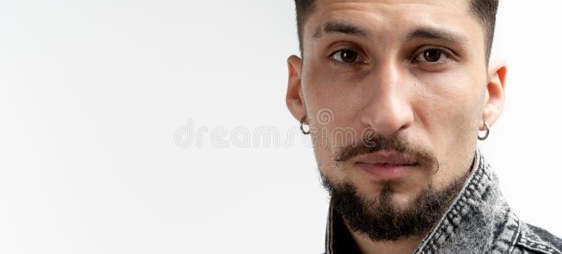 Ritratto alto vicino di giovane uomo barbuto serio in camicia del denim che esaminando la macchina fotografica isolata sopra fond fotografie stock