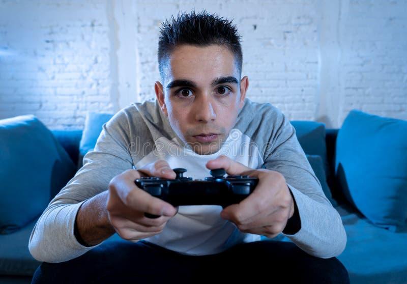 Ritratto alto vicino di giovane uomo dipendente che gioca video gioco alla notte nel concetto di dipendenza e di gioco immagini stock libere da diritti