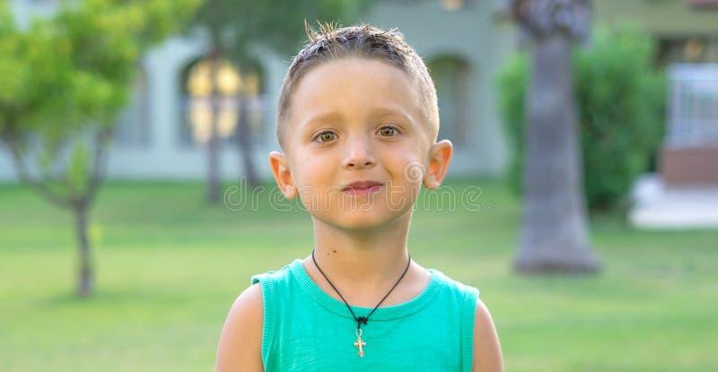 Ritratto alto vicino di un neonato europeo sorridente sorpreso che esamina macchina fotografica sopra il bambino leggero del fond immagini stock libere da diritti
