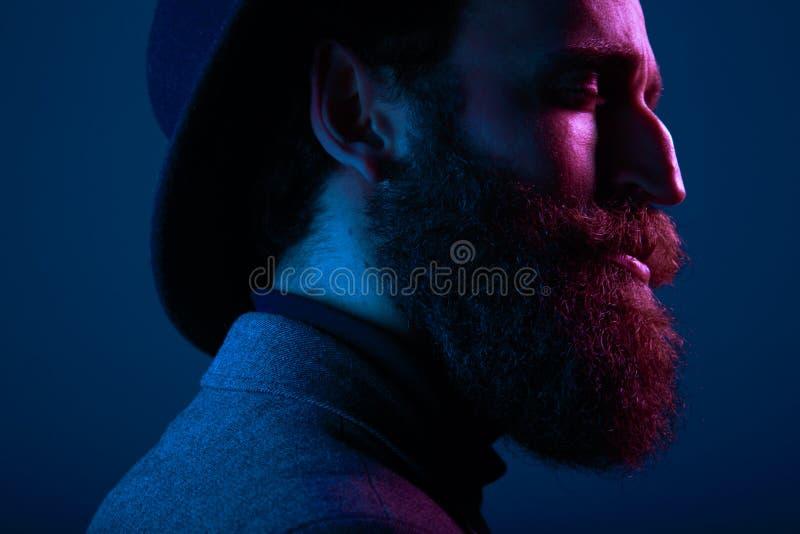Ritratto alto vicino di un uomo barbuto in cappello e del vestito, con gli occhi vicini che posano nel profilo, su fondo blu scur fotografie stock