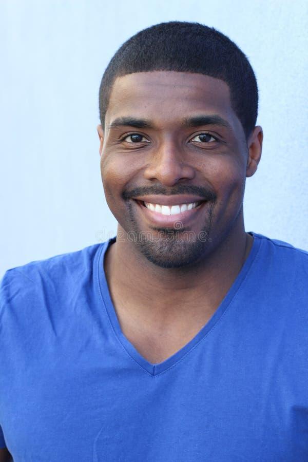 Ritratto alto vicino di verticale di un uomo di colore felice nel suo 20s con un sorriso perfetto isolato su un fondo blu fotografia stock