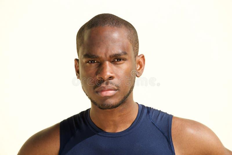 Ritratto anteriore di giovane uomo di colore serio contro fissare bianco del fondo immagine stock libera da diritti