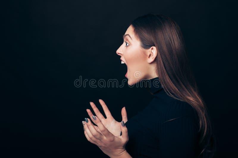 Ritratto arrabbiato di grido di profilo della donna isolato su fondo nero immagine stock