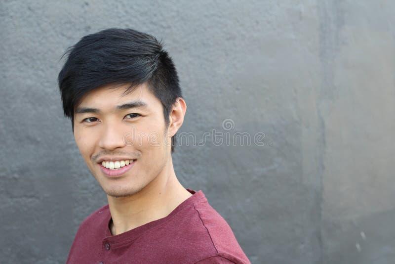 Ritratto asiatico dell'uomo che sorride isolato con lo spazio della copia per testo disponibile dal lato immagine stock