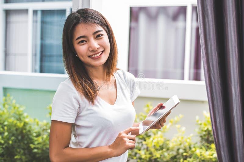 Ritratto asiatico della donna di bellezza che guarda macchina fotografica e che per mezzo della compressa per il controllo dell'o fotografia stock