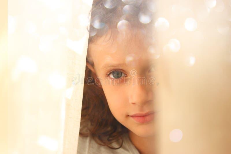 Ritratto astratto della bambina premurosa vicino alla finestra retro immagine filtrata fotografia stock