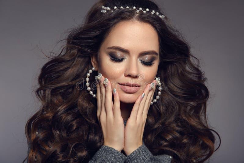 Ritratto attraente del brunette Trucco di bellezza Insieme dei gioielli delle perle Stile di capelli lungo riccio Chiodi Manicure immagine stock
