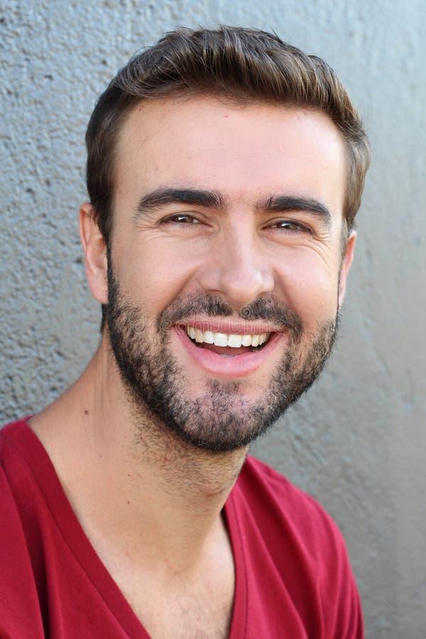 Ritratto attraente del fronte dell'uomo con un sorriso perfetto bianco isolato su un fondo grigio fotografie stock