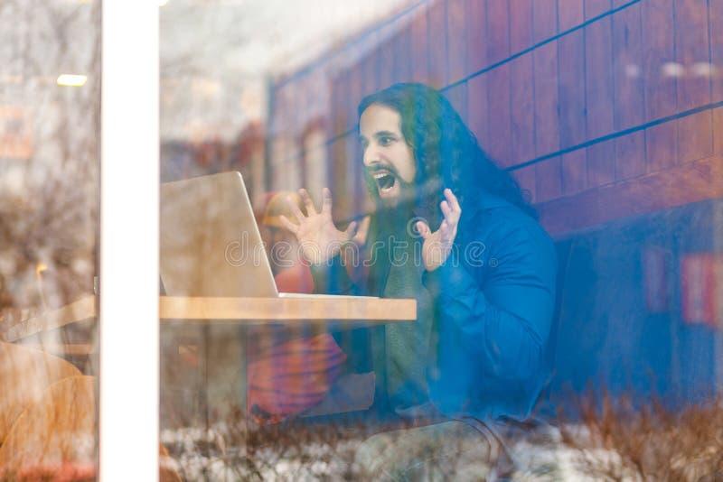 Ritratto attraverso la finestra di giovani free lance adulte aggressive arrabbiate dell'uomo nello stile casuale che si siede in  immagini stock
