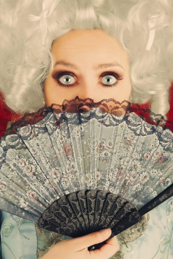Ritratto barrocco sorpreso della donna con la parrucca ed il fan immagine stock
