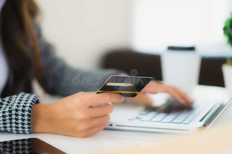 Ritratto, bella ragazza asiatica, usa una carta di credito con un portatile per fare shopping online immagini stock libere da diritti