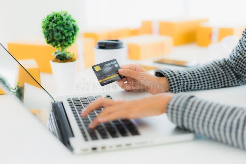 Ritratto, bella ragazza asiatica, usa una carta di credito con un portatile per fare shopping online immagini stock