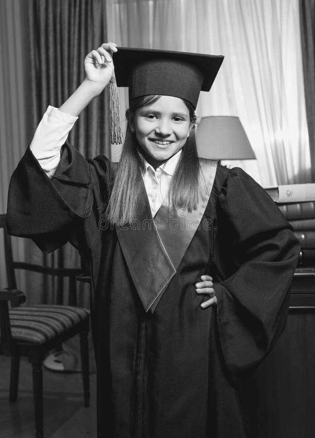 Ritratto in bianco e nero del cappuccio di graduazione della tenuta della bambina fotografia stock