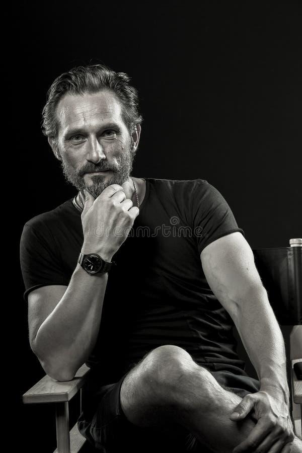 Ritratto in bianco e nero dell'uomo soddisfatto maturo che si siede sulla sedia immagini stock libere da diritti