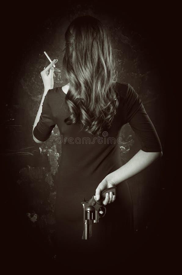 Ritratto in bianco e nero della parte posteriore pericolosa della giovane donna con capelli lunghi, vestito scuro Prende la pisto fotografie stock