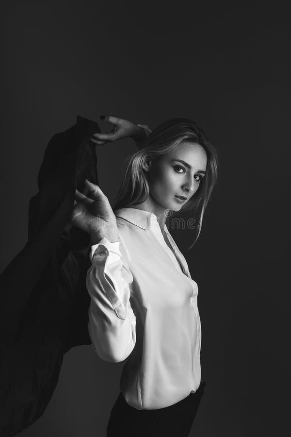 Ritratto in bianco e nero della ragazza bionda in rivestimento e camicia bianca La ragazza getta un rivestimento sulle sue spalle immagini stock