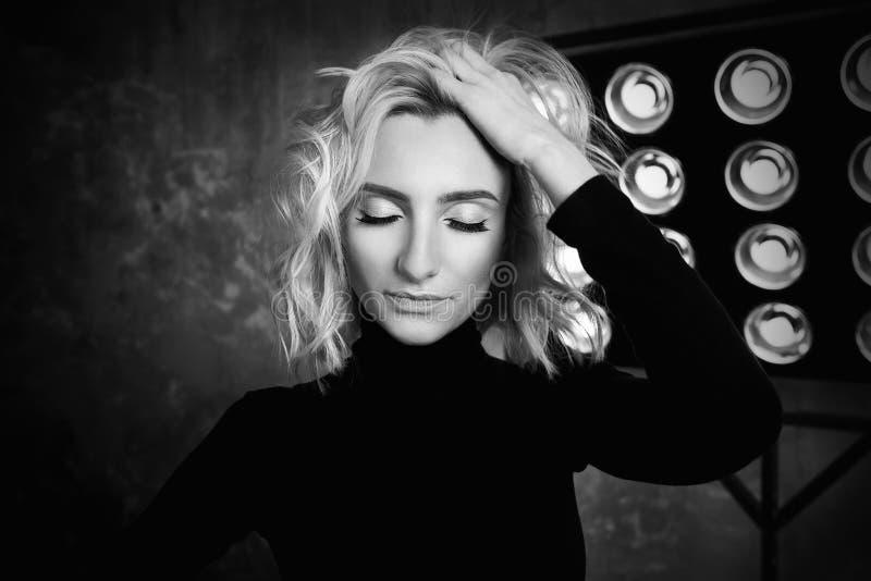 Ritratto in bianco e nero di giovane bella ragazza riccia attraente alla moda in maglione nero sulla fase fotografie stock libere da diritti