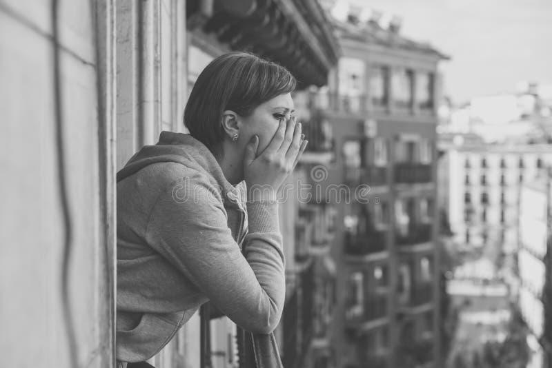 Ritratto in bianco e nero di giovane donna attraente con la depressione e l'ansia sul balcone domestico fotografia stock libera da diritti