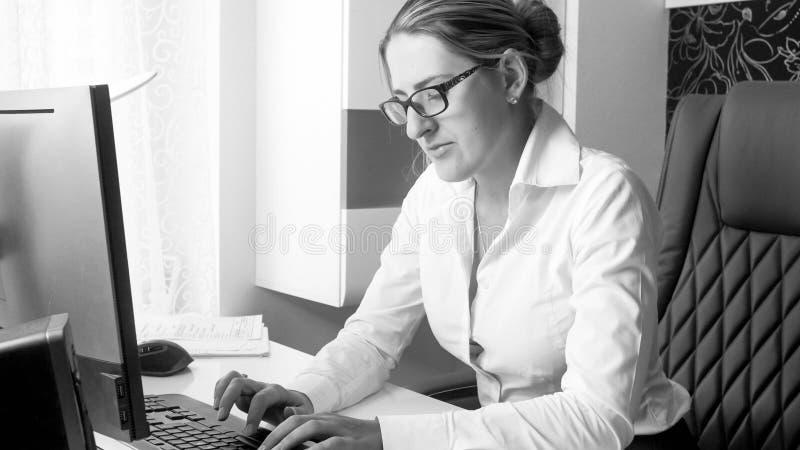 Ritratto in bianco e nero di giovane segretario che lavora al computer all'ufficio fotografia stock libera da diritti