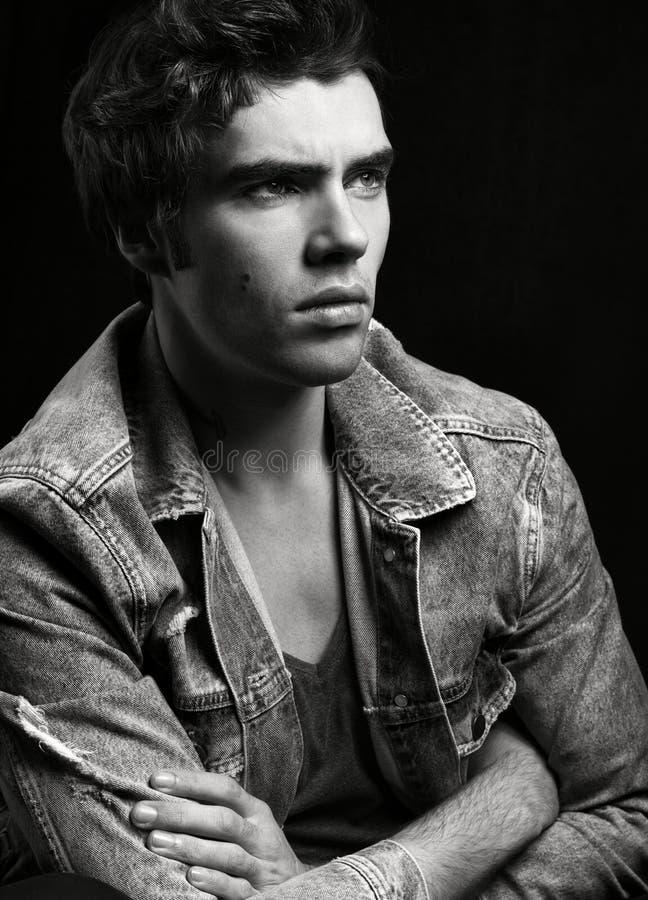 Ritratto in bianco e nero di giovane uomo bello su fondo nero immagini stock