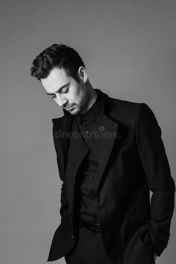 Ritratto in bianco e nero di giovane uomo bello in un vestito, condizione, mani in tasche immagini stock libere da diritti