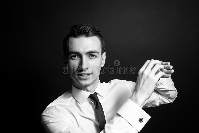 Ritratto in bianco e nero di giovane uomo d'affari in una camicia ed in uno smoking bianchi, parlante e spiegante immagini stock libere da diritti
