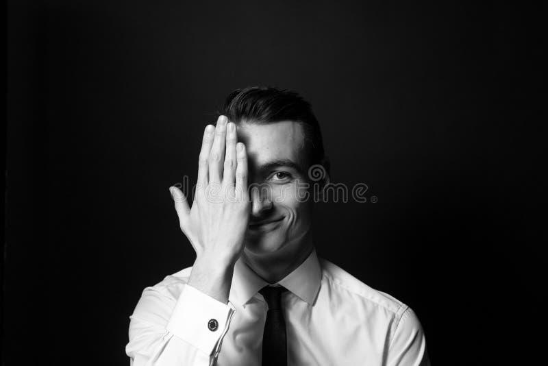 Ritratto in bianco e nero di un giovane in una camicia bianca, fronte mezzo della copertura della mano fotografie stock libere da diritti