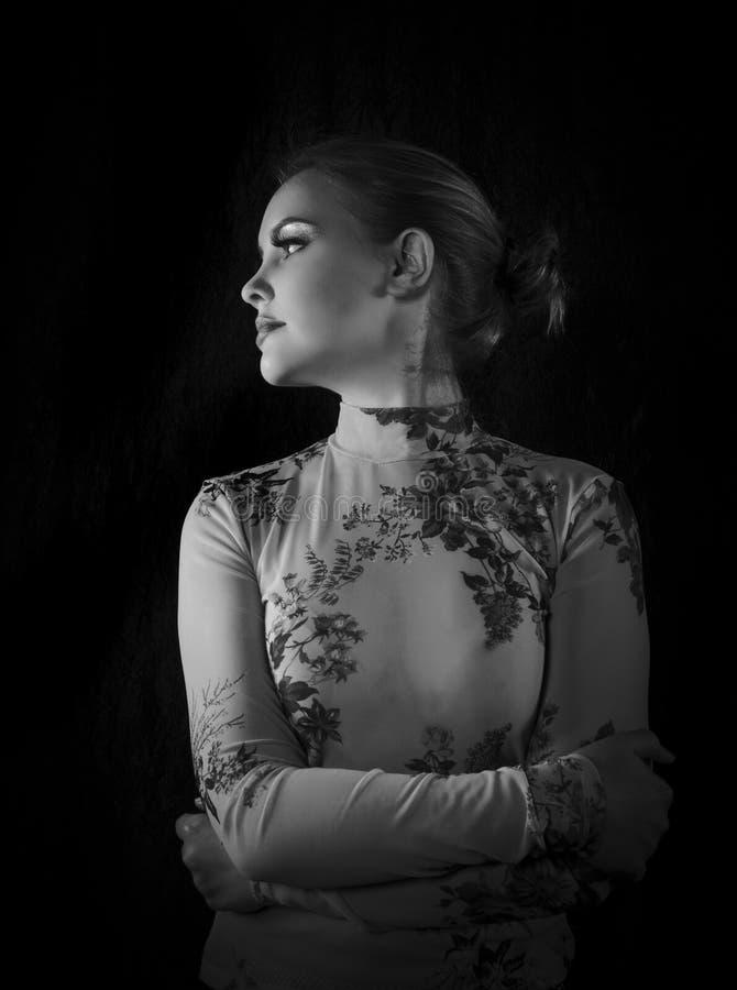 Ritratto bianco e nero di una donna bionda graziosa con una maglia floreale e i suoi capelli sollevati fotografie stock