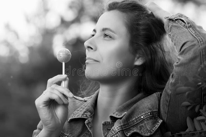 Ritratto in bianco e nero di una ragazza con la caramella del caramello su un bastone immagini stock libere da diritti