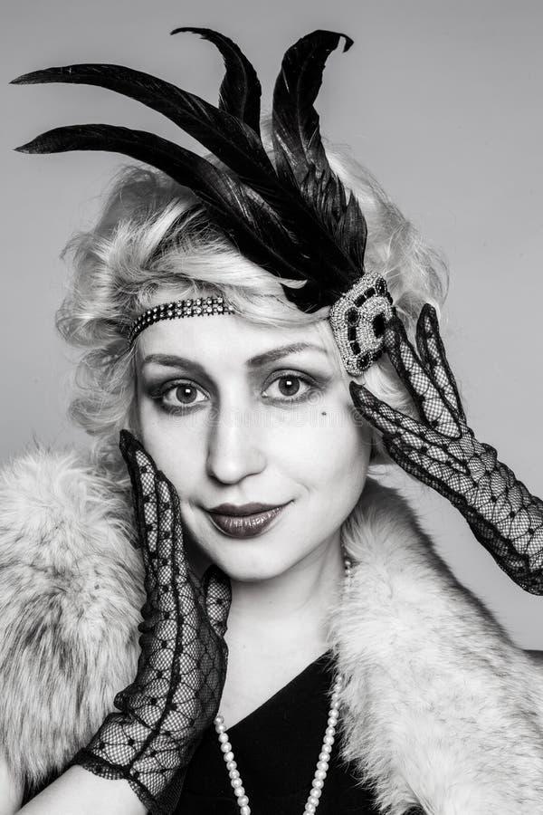 Ritratto in bianco e nero di una ragazza in un cappello con le piume ed i guanti del pizzo immagini stock