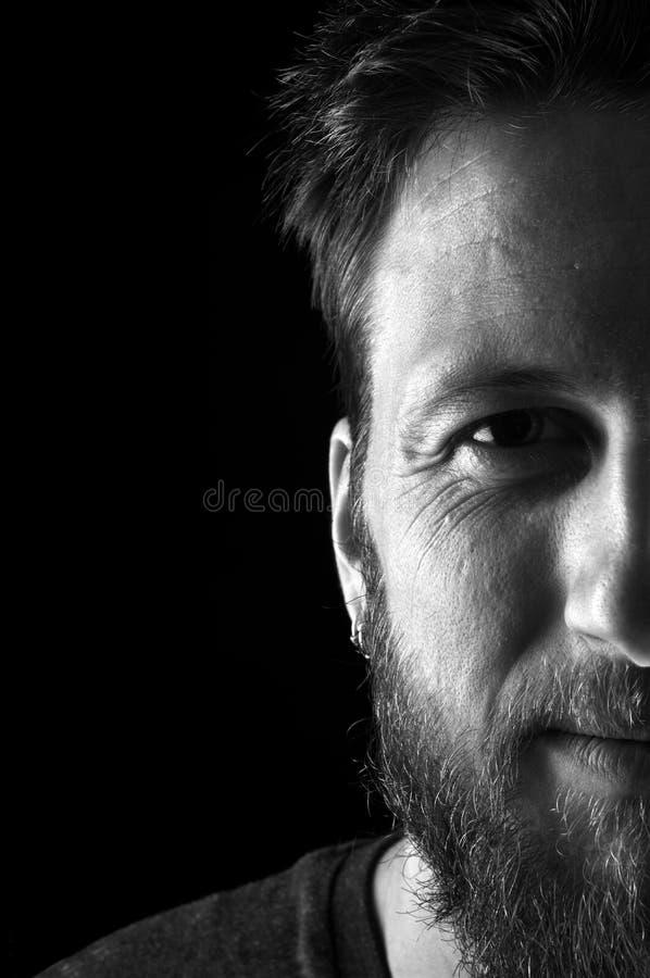 Ritratto in bianco e nero e mezzo di una fine dell'uomo sull'esame della macchina fotografica su fondo nero immagine stock