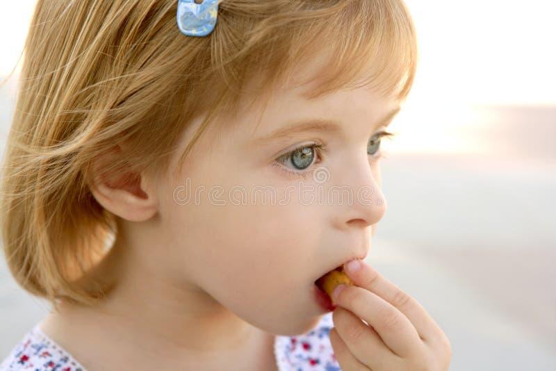 Ritratto biondo del primo piano della bambina che mangia biscotto fotografie stock libere da diritti