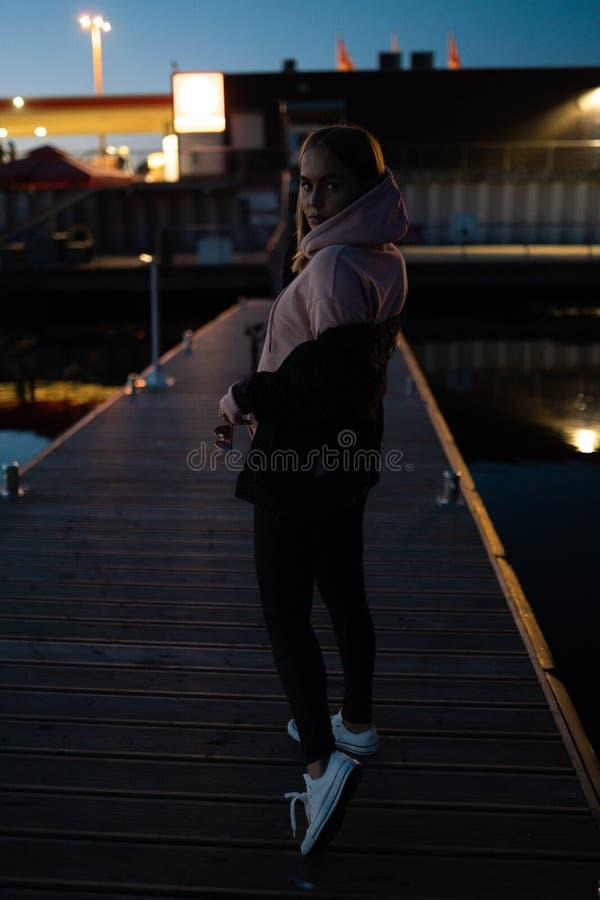 Ritratto biondo della donna che fa una pausa il fiume alla notte immagini stock libere da diritti