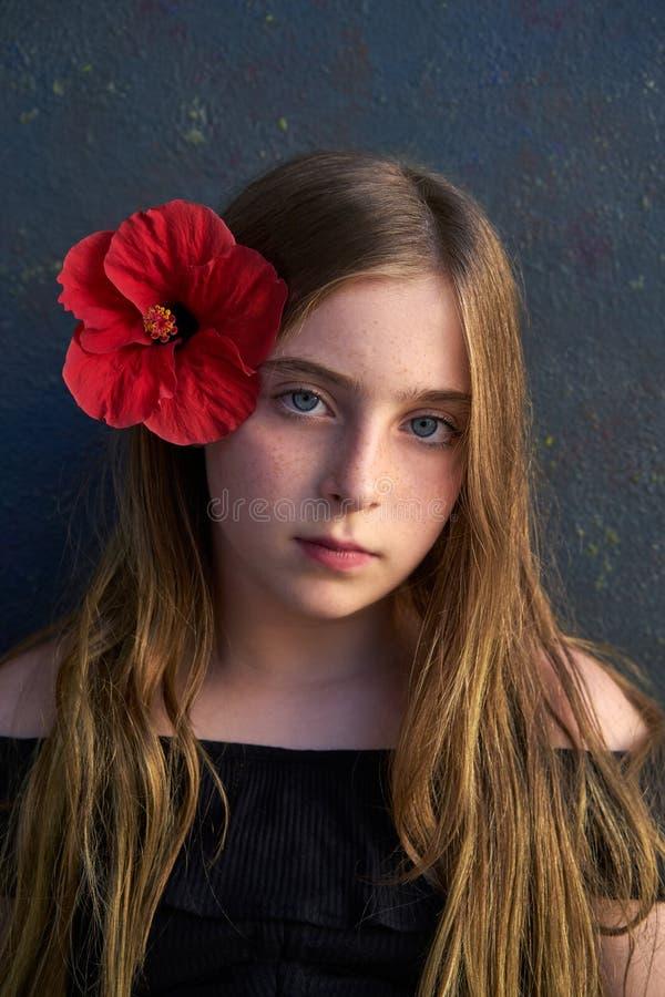 Ritratto biondo della ragazza del bambino con il fiore rosso in capelli fotografie stock