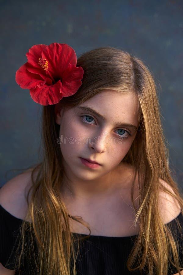 Ritratto biondo della ragazza del bambino con il fiore rosso in capelli immagini stock libere da diritti