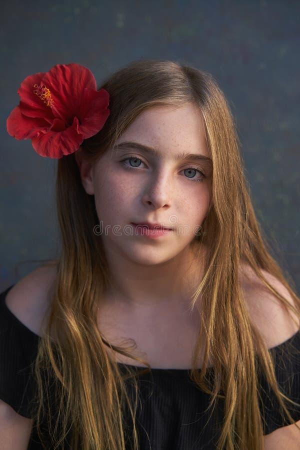 Ritratto biondo della ragazza del bambino con il fiore rosso in capelli fotografie stock libere da diritti